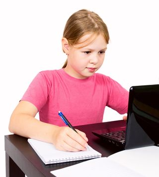 Girl using laptop & writing